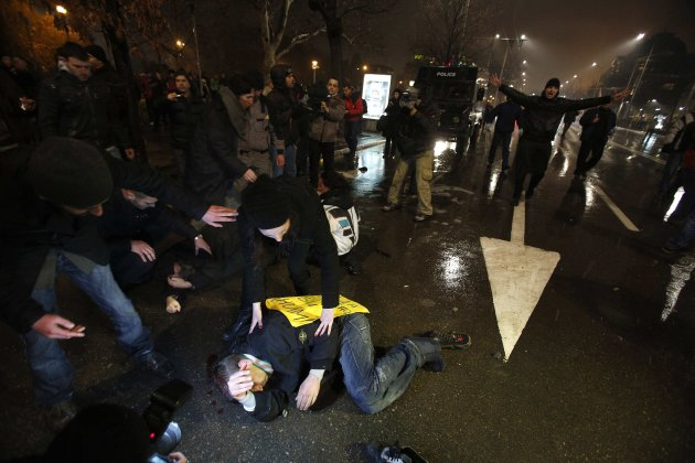 Protesters lie on the ground after clashes with riot police during a protest against high electricity prices in Sofia