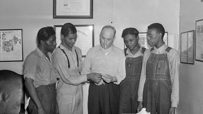 """FILE - In this July 26, 1937 file photo, New York attorney Samuel Leibowitz, center, stands in his office in New York with four of the """"Scottsboro Boys,"""" from left, Willie Robertson, Eugene Williams, Roy Wright, and Olen Montgomery. Levin is credited with saving from death all but one of the nine black teens who were wrongly convicted of raping two white women in 1931. In a final chapter to one of the most important civil rights episodes in American history, Alabama lawmakers voted Thursday, April 4, 2013 to give posthumous pardons to the """"Scottsboro Boys"""". (AP Photo, File)"""