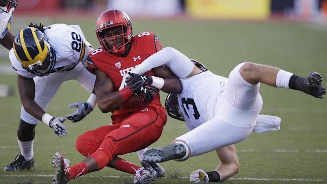 Utah wide receiver Bubba Poole (8) is tackled by Michigan's Jarrod Wilson (22) and teammate Desmond Morgan (3) in the first quarter during an NCAA college football game, Thursday, Sept. 3, 2015, in Salt Lake City. (AP Photo/Rick Bowmer)