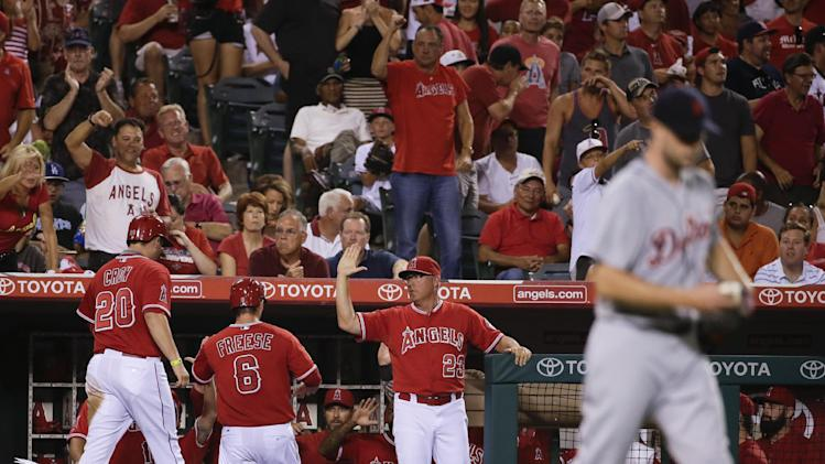 Los Angeles Angels' C.J. Cron, left, and David Freese are greeted in the dugout after scoring on a hit by Kole Calhoun as Detroit Tigers starting pitcher Max Scherzer walks to the mound during the fifth inning of a baseball game in Anaheim, Calif., Thursday, July 24, 2014. (AP Photo/Chris Carlson)