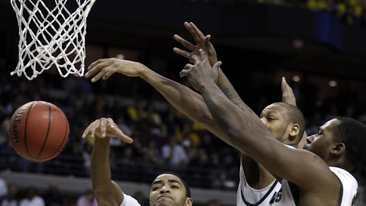 Memphis guard Geron Johnson (55) is defended by Michigan State guard Gary Harris, from left, forward Adreian Payne and Derrick Nix during the first half of their third-round game of the NCAA college basketball tournament in Auburn Hills, Mich., Saturday March 23, 2013.  (AP Photo/Paul Sancya)