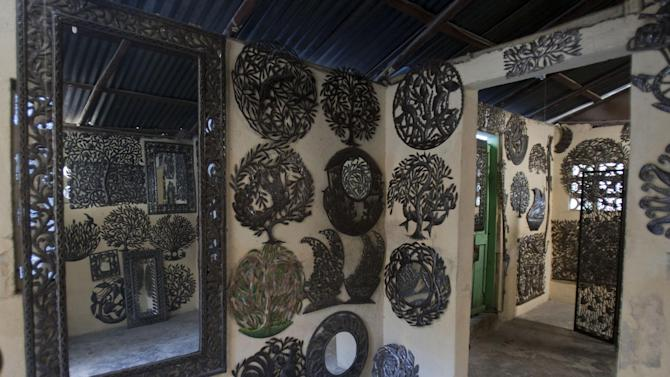 In this Dec. 8, 2012 photo, arts and crafts hang for sale in the Jacques Rony's shop in Croix-des-Bouquets, Haiti.  Haitian crafts reached their peak in the early 1980s when thousands were employed. But the industry, and the rest of Haiti's economy, collapsed following a United Nations-imposed embargo in 1993 that sought to restore constitutional rule after a military junta ousted then-President Jean-Bertrand Aristide (AP Photo/Dieu Nalio Chery)
