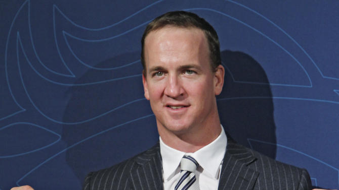 March 20 New Denver Broncos quarterback Peyton Manning holds a Broncos jersey with his name and number at the conclusion of an NFL football news conference at the Broncos headquarters in Englewood, Colo.,  on Tuesday, March 20, 2012.  (AP Photo/Ed Andrieski)