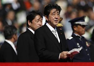 Japanese Prime Minister Shinzo Abe (C), flanked by Defence Minister Itsunori Onodera (2nd L), delivers a speech as he reviews Japan Self-Defence Forces' (SDF) troops during the annual SDF ceremony at Asaka Base in Asaka, near Tokyo October 27, 2013. REUTERS/Issei Kato