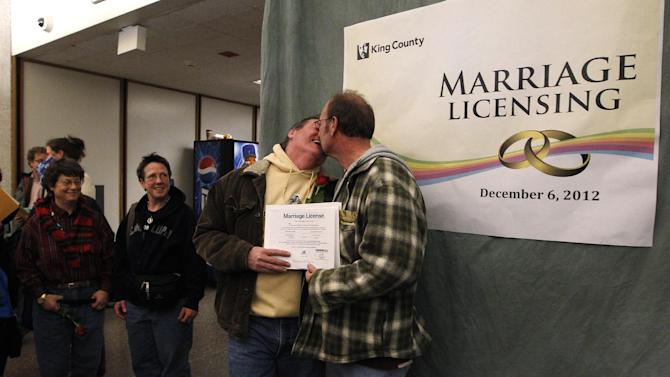 Bret Goodwin, right, kisses his partner Andy Goodwin in the lobby of the King County Administration Building shortly after the couple received one of the first same-sex marriage licenses issued in the state early Thursday morning, Dec. 6, 2012, in Seattle. King County Administrator Dow Constantine began issuing the licenses immediately upon certification of the November election that passed Referendum 74, just after midnight. (AP Photo/Elaine Thompson)