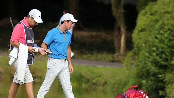 Rory McIlroy (centre) leaves the 18th green on the second day's play of the Irish Open at the Fota Island Resort in Cork, Ireland, on June 20, 2014