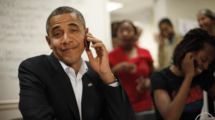 President Barack Obama reacts after realizing he dialed the wrong number while making calls from a local campaign field office during a unscheduled visit, Sunday, Oct. 28, 2012 in Orlando, Fla. (AP Photo/Pablo Martinez Monsivais)