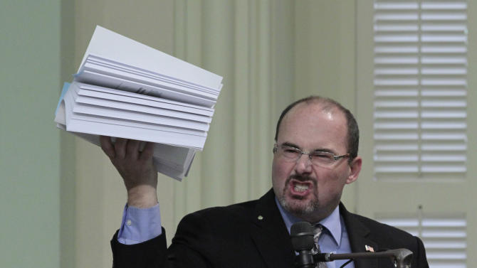 Assemblyman Tim Donnelly, R-Twin Peaks, holds up a copy of the state budget as he urges lawmakers to reject the 2012-13 spending plan at the state Capitol in Sacramento, Calif., Friday, June 15, 2012. Despite opposition by Republicans, the Assembly approved the budget 50-25 and sent it to the governor. (AP Photo/Rich Pedroncelli)