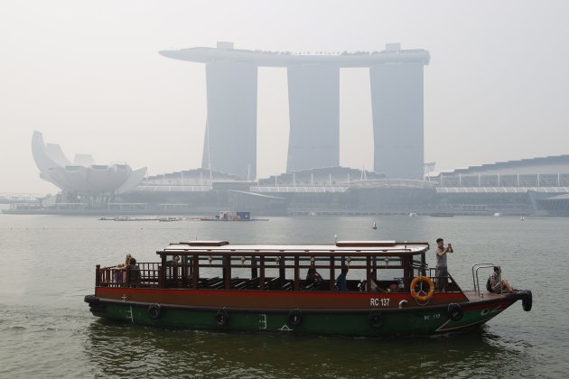A tourist bumboat cruises past the hazy skyline of the Marina Bay Sands casino and resort in Singapore