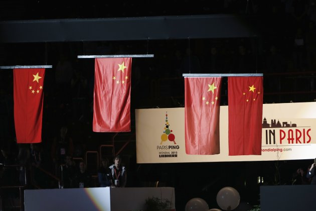 China's flags are lifted up during the podium ceremony of men's singles final at the World Team Table Tennis Championships in Paris