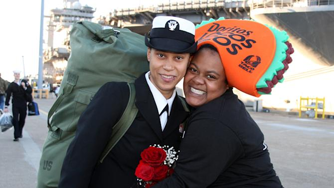 IMAGE DISTRIBUTED FOR TACO BELL - Taco Bell employee Shantice Reagan from store #2709 hugs a sailor while handing out free Doritos Locos Tacos during the return of the USS Eisenhower Carrier Strike Group at the Naval Station in Norfolk, Va., on Wednesday, Dec. 19, 2012. In gratitude for their service, Taco Bell provided the sailors and their families with their first meal after returning from six months of operations in the Middle East. (Lisa Billings/AP Images for Taco Bell)