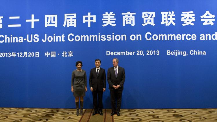Officials pose for photos before the opening meeting session of the 24th China-U.S. Joint Commission on Commerce and Trade held at Diaoyutai State Guesthouse in Beijing