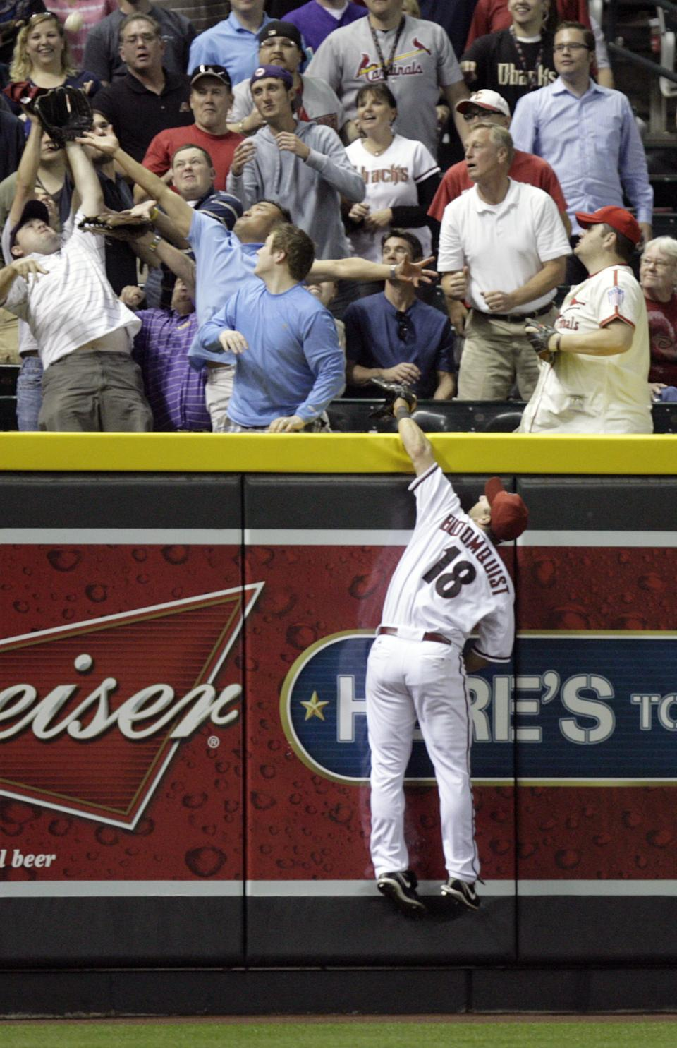 Arizona Diamondbacks left fielder Willie Bloomquist leaps for but can only watch as a ball hit for a home run by St. Louis Cardinals' Lance Berkman lands in the crowd in the seventh inning of an MLB baseball game Monday, April 11, 2011, in Phoenix. (AP Photo/Paul Connors)