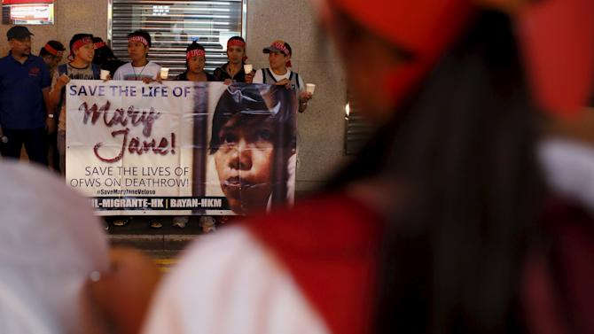 Filipinas carry a banner as they appeal for the pardon of Mary Jane Veloso outside the Indonesian consulate in Hong Kong