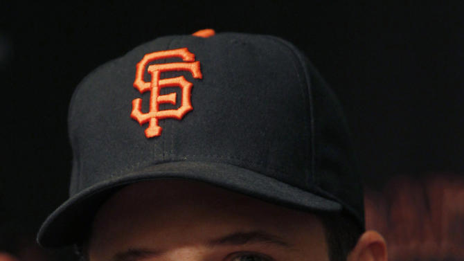 San Francisco Giants' Buster Posey smiles during a news conference, Friday, March 29, 2013, in San Francisco. Posey and the Giants have agreed to a $167 million, nine-year contract, a deal that includes a club option for 2022 that could raise the value to $186 million over a decade.(AP Photo/George Nikitin)