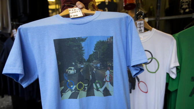 """In this photo taken Monday, July 16, 2012, a t-shirt with featuring the cover photograph from the album """"Abbey Road"""" printed on it, shows The Beatles holding Olympic rings as they walk across the zebra crossing as it sold at a London market. The guardians of the games are vigilant about protecting the integrity - and the commercial clout - of the Olympic brand. But even they can't stop the irreverent spirit of artists and craftspeople, who have responded to the games with a cheeky mix of celebration, skepticism and satire. (AP Photo/Matt Dunham)"""