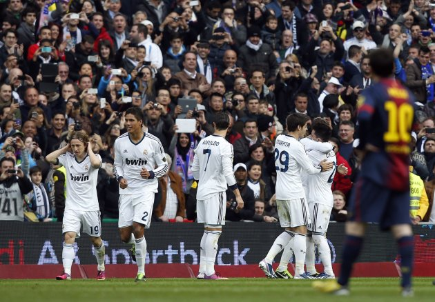 Real Madrid players celebrate Ramos' goal as Barcelona's Messi reacts during their Spanish first division soccer match in Madrid