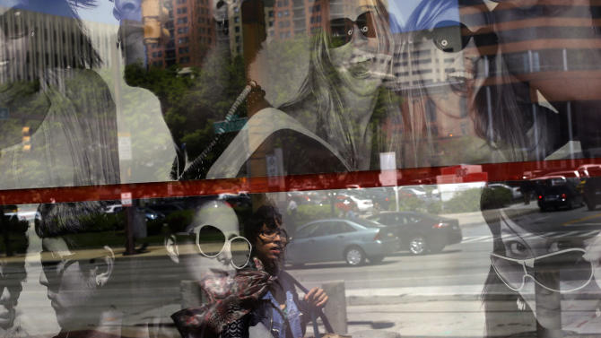 In this April 25, 2013 photo, a woman is reflected in a retail store's window display in Baltimore. The private Conference Board reports on consumer confidence for April on Tuesday, April 30, 2013.(AP Photo/Patrick Semansky)
