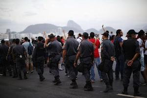An anti-FIFA World Cup demonstrator takes part in a march at Copacabana beach in Rio de Janeiro