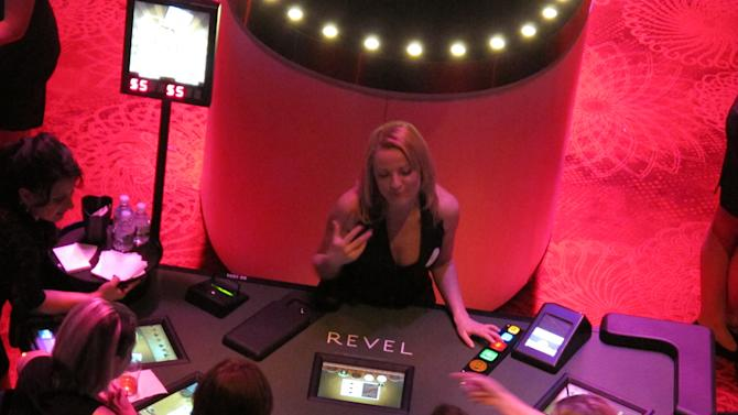 In this March 28, 2012, photo, Ludmilla Kaliafa, an E-Dealer at Revel in Atlantic City N.J., chats with gamblers on the first night the $2.4 billion casino resort allowed people to gamble. It was the first of three invitation-only test nights before Revel opens to the public on Monday, April 2. (AP Photo/Wayne Parry)
