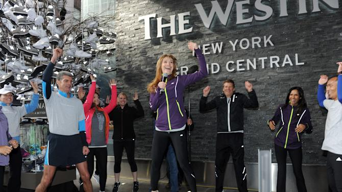 IMAGE DISTRIBUTED FOR WESTIN - Padma Lakshmi, right, joins Brian Povinelli, second right, Global Brand Leader, Westin Hotels & Resorts, as Holly Perkins, center, New Balance Fitness Ambassador, leads a warm-up stretch on Thursday, Nov. 15, 2012 to kick off the New York City 5K run in celebration of the global launch of Westin's New Balance gear lending program.  Thousands of associates around the world ran in support of the brands' pledge to donate 15,000 pairs of shoes to Soles4Souls and Hurricane Sandy relief. (Photo by Diane Bondareff/Invision for Westin/AP Images)