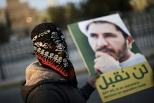 A protester holds a placard depicting Sheikh Ali Salman,…