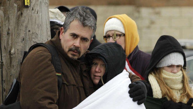 Bundled from the cold, people line the street outside St. Mary's Church before funeral services for 16-year-old Daniel Parmertor  in Chardon, Ohio on Saturday, March 3, 2012.  Parmertor and two other students were fatally shot Monday at Chardon High School.  Two other students were also shot in the incident. (AP Photo/Amy Sancetta)