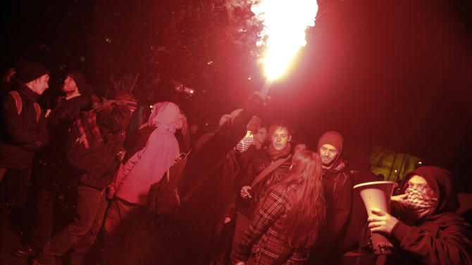 Protesters fire flares during an anti government protest in Ljubljana, Slovenia, Friday, Feb. 8, 2013. Thousands gathered to protest against the Janez Jansa led government and their policies. (AP Photo/Darko Bandic)