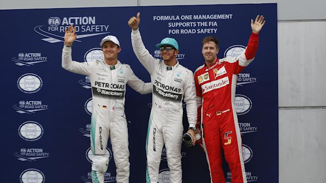 Mercedes driver Lewis Hamilton, center, of Britain poses with teammate Nico Rosberg, left, of Germany and Ferrari driver Sebastian Vettel of Germany after qualifying for the Malaysian Formula One Grand Prix at Sepang International Circuit in Sepang, Malaysia, Saturday, March 28, 2015. Hamilton took pole position for Sunday's race ahead of Vettel. Rosberg finished third. (AP Photo/Vincent Thian)