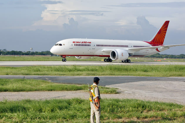A security personnel stands guard as the Air India's Dreamliner Boeing 787 taxies upon its arrival at the airport in New Delhi