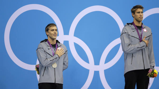 United States silver medalist Nick Thoman, left, and gold medalist Matthew Grevers, right, listen to the U.S. national anthem during a ceremony following their wins in the men's 100-meter backstroke swimming final at the Aquatics Centre in the Olympic Park during the 2012 Summer Olympics in London, Monday, July 30, 2012. (AP Photo/Matt Slocum)
