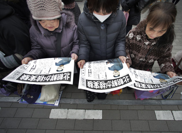 Women read copies of a delivered extra edition of a Japanese newspaper reporting North Korea's nuclear test, in Tokyo Tuesday, Feb. 12, 2013. North Korea said it successfully detonated a miniaturized