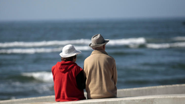 In this Nov. 29, 2012 photo, an elderly couple looks out onto La Boca from a pedestrian walkway in Navidad, Chile. An 8.8-magnitude earthquake and the tsunami it triggered on Chile's coasts in 2010, killed 551 people, destroyed 220,000 homes and washed away docks, river fronts and seaside resorts. Most Navidenos were left without power and water for a month; many lost their homes. (AP Photo/Luis Hidalgo)