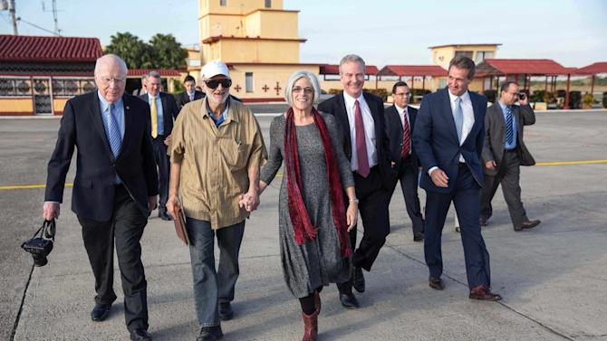 Alan Gross walks across the airport tarmac with his wife, Judy Gross and Senator Patrick Leahy, (D-VT),  Rep. Chris Van Hollen (D-MD) and Senator Jeff Flake (R-AZ) during his release at an airport near Havana, Cuba in this  White House handout photo