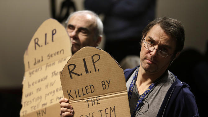 Protesters display placards while demonstrating during an address by House majority leader Eric Cantor, of Va., at the John F. Kennedy School of Government at Harvard University, in Cambridge, Mass., Monday, March 11, 2013. The demonstrators called attention to what they describe as Cantor's opposition to funding syringe exchange programs for people with HIV and AIDS. (AP Photo/Steven Senne)