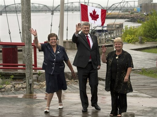 Prime Minister Stephen Harper, Tilly O'Neill Gordon, left, MP for Miramichi, and Fisheries Minister Gail Shea, right, wave as they walk on a boardwalk in Miramichi, N.B. on Friday, Aug. 9, 2013. THE CANADIAN PRESS/Andrew Vaughan
