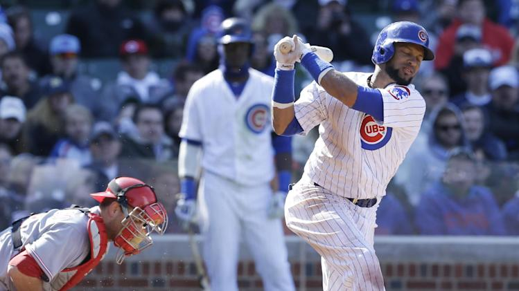 Chicago Cubs' Emilio Bonifacio, right, strikes out swinging during the seventh inning of a baseball game against the Cincinnati Reds in Chicago, Friday, April  18, 2014. The Reds won 4-1
