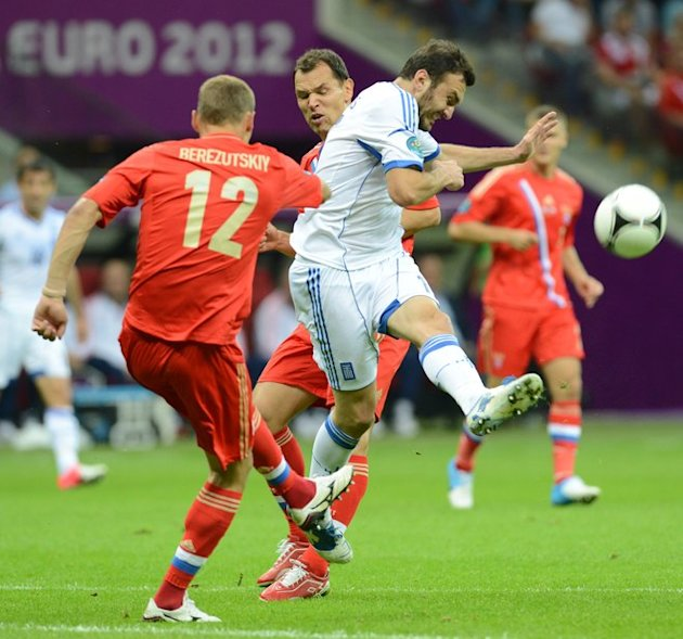 Russian Defender Aleksei Berezutski (L) Kicks The Ball At The Euro 2012 Championships Football Match Greece Vs Russia AFP/Getty Images