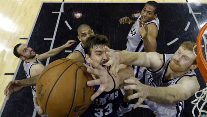 Memphis Grizzlies' Marc Gasol, center, is defended by, from left to right, San Antonio Spurs' Manu Ginobili, Tim Duncan, Kawhi Leonard and Matt Bonner during the first half in Game 1 of a Western Conference Finals NBA basketball playoff series on Sunday, May 19, 2013, in San Antonio. (AP Photo/Eric Gay)