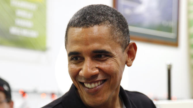 President Barack Obama smiles with a shave Ice at Island Snow at Kailua Beach Center while on vacation with the first family in Kailua, Hawaii, Monday, Dec. 27, 2010. (AP Photo/Carolyn Kaster)