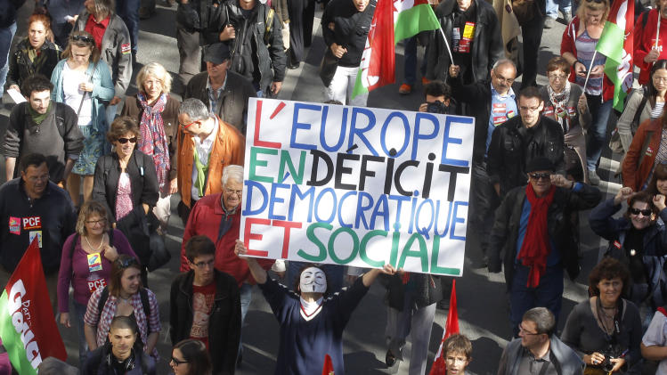"""A demonstrator holds a placard which reads: """"Europe in Social and Democratic Deficit"""" during a rally to protest against the austerity measures announced by the French government, in Paris, Sunday, Sept. 30, 2012. (AP Photo/Michel Euler)"""