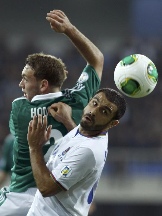 Sadygov of Azerbaijan is challenged by Hodson of Northern Ireland during their 2014 World Cup qualifying soccer match in Baku