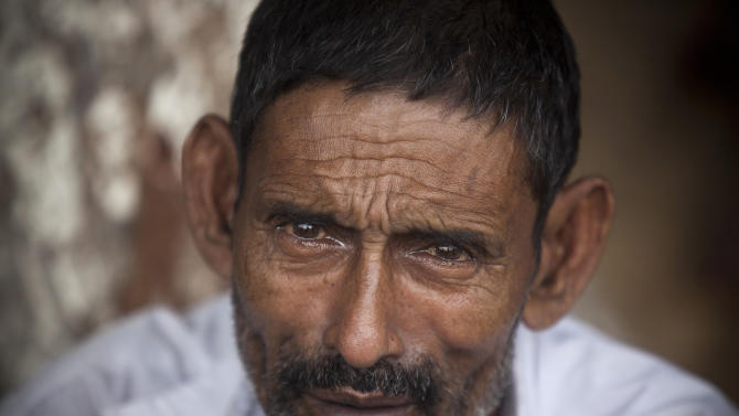 Tears fill the eyes of a Bangladeshi father who is looking for his son missing in the April 24 garment factory building collapse in Savar, near Dhaka, Bangladesh, Sunday, May 12, 2013. Search teams resumed their rain-interrupted work Sunday as the death toll from the collapse continued to climb past 1,100. (AP Photo/Ismail Ferdous)