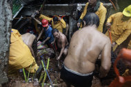 Filipino volunteers dig for survivors where four homes collapsed in a landslide in Quezon City, north of Manila, Philippines, Tuesday, Aug. 7, 2012. Relentless rains submerged half of the sprawling Philippine capital, triggered a landslide that killed several people and sent emergency crews scrambling Tuesday to rescue and evacuate tens of thousands of residents. (AP Photo/John Javellana)