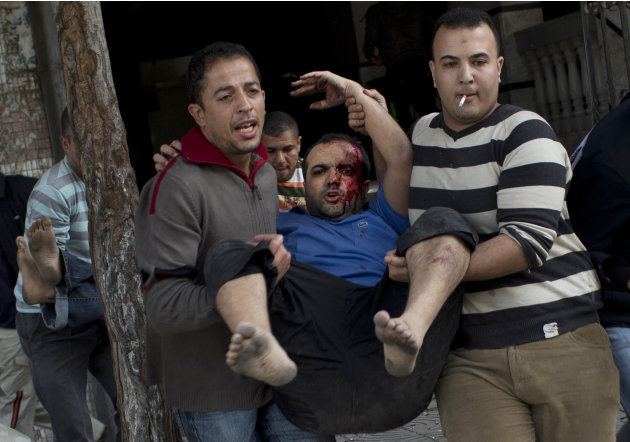 Palestinians carry injured people out of a media center in Gaza City that was hit by an Israeli strike for the second time in two days Monday, Nov. 19, 2012. Palestinian militant group Islamic Jihad s