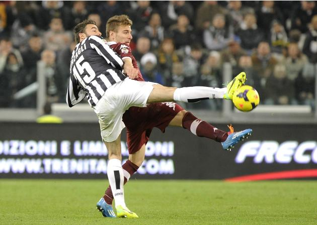 Juventus' Andrea Barzagli fights for the ball with Torino's Ciro Immobile during their Italian Serie A soccer match in Turin