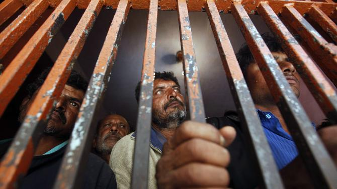 Fishermen from India stand behind bars in a cell, after being detained in Pakistani waters, at a police station in Karachi