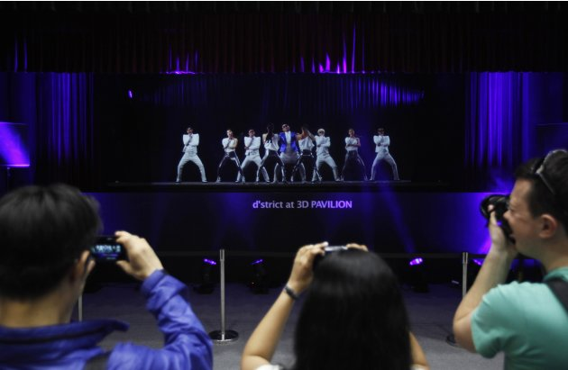 Visitors take photographs of PSY's hologram show during World IT show 2013 at the Coex convention centre in Seoul