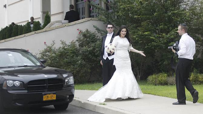 An unidentified bride and groom react at a Jewish wedding as the motorcade of Republican presidential candidate and former Massachusetts Gov. Mitt Romney drives past for a campaign fundraising event in Lakewood, N.J., Wednesday, Aug. 8, 2012. Romney's motorcade rolled into the fundraiser as a bride and groom were posing for pictures in the parking lot outside the hall in Lakewood. Several guests in yarmulkes who were standing around turned their cameras away from the couple, and a few chased the motorcade around the corner.(AP Photo/Charles Dharapak)