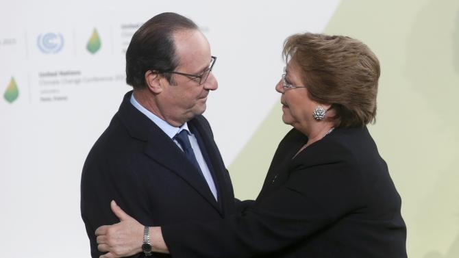 French President Hollande welcomes Chile's President Bachelet as she arrives for the opening day of the World Climate Change Conference 2015 (COP21) at Le Bourget, near Paris